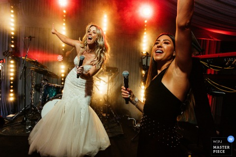 Manchester, England indoor wedding reception party award-winning picture showing the Bride dancing and singing on stage. The world's most skilled wedding photographers are members of the WPJA
