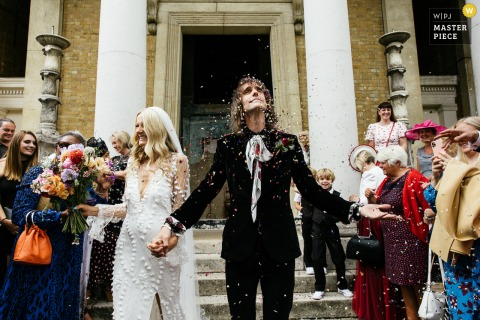 Manchester, UK indoor wedding reception party award-winning picture showing the groom getting showered in confetti. The world's most skilled wedding photographers are members of the WPJA