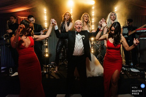 Manchester, England indoor wedding reception party award-winning picture showing brides dad dancing with bridesmaids. The world's most skilled wedding photographers are members of the WPJA
