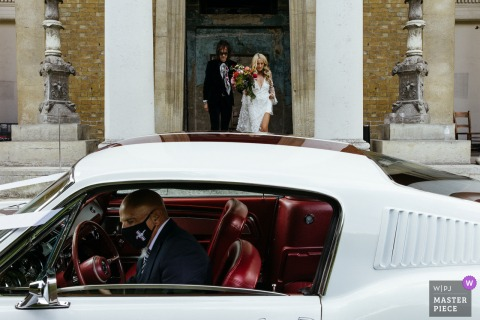 London, England marriage ceremony award-winning image showing couple heading out to the wedding car. The world's best wedding picture competitions are featured via theWPJA
