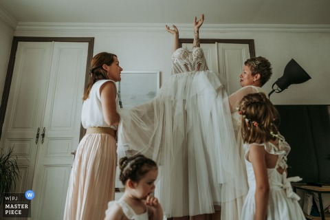 Saint Porchaire, Charente-Maritime marriage preparation time award-winning picture capturing The bride putting on her dress. The world's best wedding image competitions are held by the WPJA
