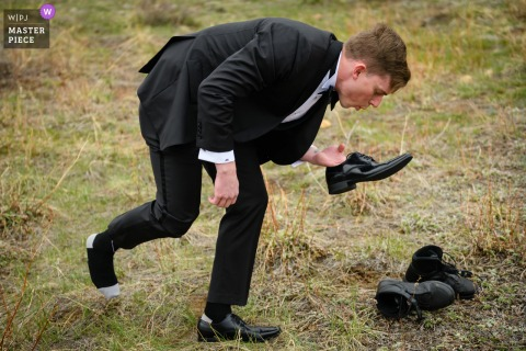 Estes Park, Colorado nuptial day award-winning image of Groom blowing on his shoe to clean it after changing out of his motorcycle boots