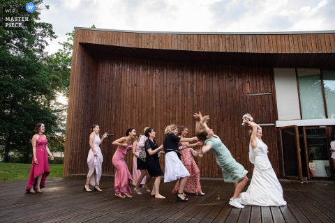 Grand Est outdoor marriage reception party award-winning photo that has recorded A girl falling for the bouquet. The world's top wedding photographers compete at the WPJA
