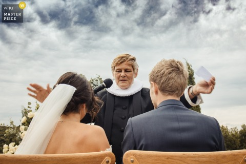 Domaine des Grillions, Drome  outdoor marriage ceremony award-winning image showing The master of ceremonies blesses the bride and groom. The world's best wedding photo contests presented by the WPJA