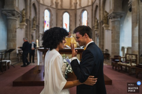 Saint Cast, France indoor marriage ceremony award-winning image showing the couple in the church Just married. The world's best wedding picture competitions are featured via theWPJA