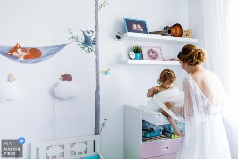 Tiempo de preparación para el matrimonio de Bucarest imagen premiada que captura a la novia preparando a su hija. La WPJA organiza los mejores concursos de imágenes de bodas del mundo