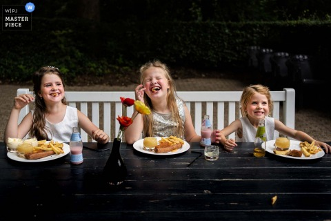 Residence Rhenen, Netherlands indoor wedding reception party award-winning picture showing The girls are heaving fun during their kids meal.