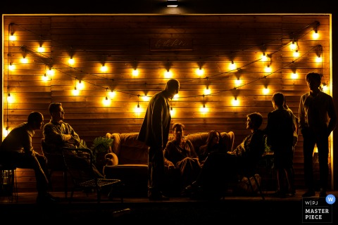 By the Lake barn, Romania indoor wedding reception party award-winning picture showing father of the groom and family under strings of lights. The world's most skilled wedding photographers are members of the WPJA