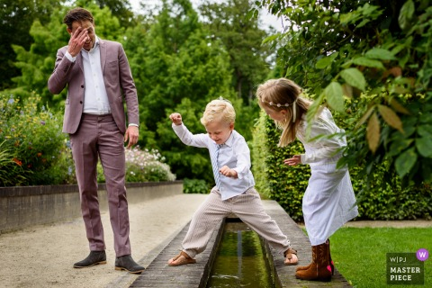 Noord Brabant nuptial day award-winning image of a Young brides man jumping over water, as bridesmaid checks him out, father frowns - from the world's best wedding photography competitions hosted by the WPJA