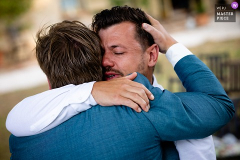 Urbino, Italy nuptial day award-winning image of the groom and friend hugging outside - from the world's best wedding photography competitions hosted by the WPJA
