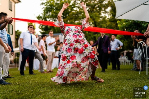 Villa Rigatti, Fiumicello, Udine marriage reception party award-winning photo that has recorded the outdoor Limbo game on the grass - from the world's best wedding photography competitions offered by the WPJA