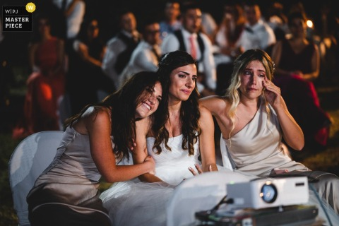Fattoria di Casalappi, Tuscany marriage reception party award-winning photo that has recorded the Bride and bridesmaids watching an emotional video - from the world's best wedding photography competitions offered by the WPJA