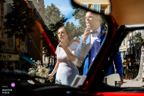 Paris nuptial day award-winning image of The bride and groom eating ice cream while they wait for the driver - from the world's best wedding photography competitions hosted by the WPJA