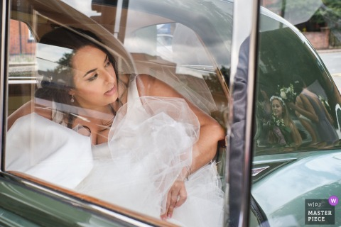 St. Mary's Catholic Church, Loughborough nuptial day award-winning image of The bride exiting the car, while one of the flower girls watches, reflected in the rear of the car