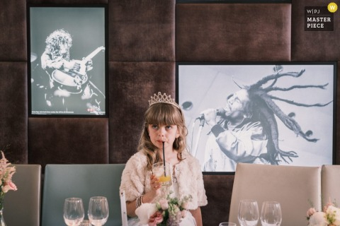 Frederick's, Camden, London marriage reception party award-winning photo that has recorded The flower girl from the wedding sipping a drink with an innocent expression, against a background of iconic imagery from the world of popular music