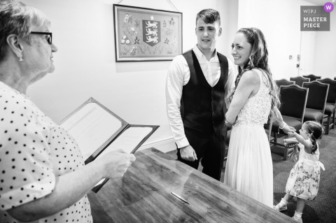 The Greffe, Guernsey marriage ceremony award-winning image showing the Couples daughter wanting attention during the indoor event - from the world's best wedding photography competitions presented by the WPJA