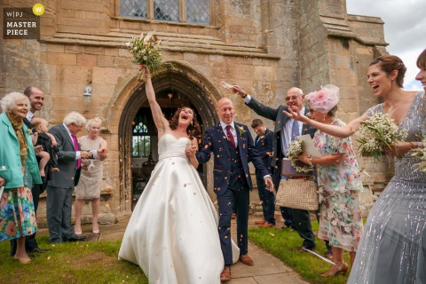 East Midlands marriage ceremony award-winning image showing the Happy couple coming out of the church - from the world's best wedding photography competitions presented by the WPJA