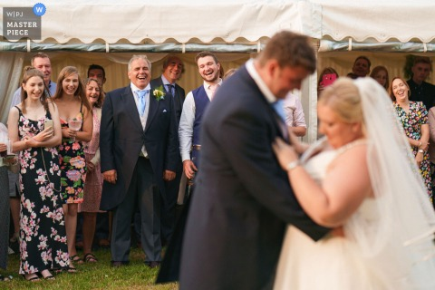 Lincolnshire marriage reception party award-winning photo that has recorded the Father of bride and guests looking on towards bride and grooms first dance - from the world's best wedding photography competitions offered by the WPJA