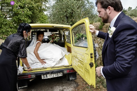 Pieve di San Pietro, Gropina nuptial day award-winning image of the bride leaving the church in the back of the car after the ceremony - from the world's best wedding photography competitions hosted by the WPJA
