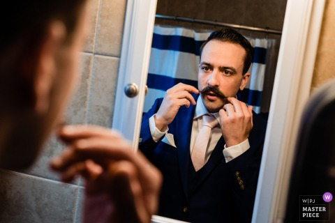 Pennsylvania getting ready for marriage award-winning picture capturing the Groom doing one final mustache check before heading off to the ceremony - from the world's best wedding photography competitions held by the WPJA