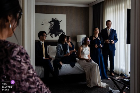 Philadelphia getting ready for marriage award-winning picture capturing the Mother of the bride nervously watching her daughter/bride play super smash bros with her wedding party when she knows they should be leaving for the ceremony