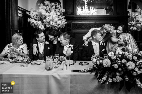 Whitley Hall, England marriage reception party award-winning photo that has recorded The bride and groom and guests chat and congratulate each other after some wonderful speeches - from the world's best wedding photography competitions offered by the WPJA