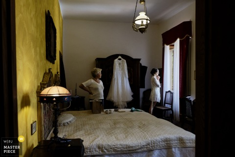 Abbazia Santo Spirito, Comignago getting ready for marriage award-winning picture capturing the Bride looking out the window - from the world's best wedding photography competitions held by the WPJA