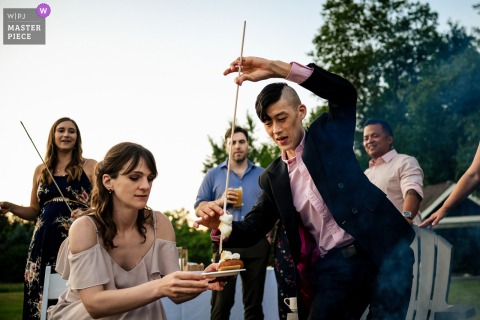 1824 House - Waitsfield, Vermont marriage reception party award-winning photo that has recorded Guests making s'mores over a fire during the reception - from the world's best wedding photography competitions offered by the WPJA