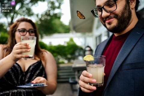 Essex Resort - Essex, Vermont marriage reception party award-winning photo that has recorded A butterfly that visited the cocktail hour interested in a guests drink - from the world's best wedding photography competitions offered by the WPJA