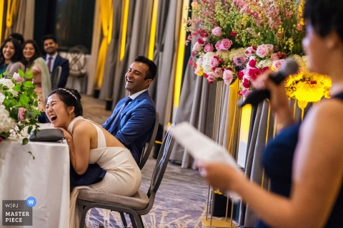 The Westin St. Francis, San Francisco marriage reception party award-winning photo that has recorded The bride and groom laughing during a toast by the maid of honor - from the world's best wedding photography competitions offered by the WPJA