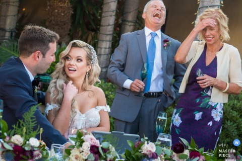 Casa Romantica, San Clemente marriage reception party award-winning photo that has recorded The parents of the bride and groom react to a remote speech delivered by Zoom on Ipad - from the world's best wedding photography competitions offered by the WPJA