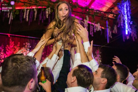 Chaparral Ranch, Aspen, Colorado marriage reception party award-winning photo that has recorded The bride gets lifted by several men on the dance floor - from the world's best wedding photography competitions offered by the WPJA