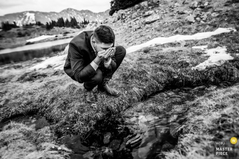 Loveland Pass, Colorado nuptial day award-winning image of the Groom drinking water at a stream - from the world's best wedding photography competitions hosted by the WPJA