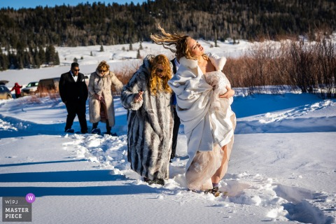 Pagosa Springs, CO nuptial day award-winning image of Bride flipping her hair while walking through snow on her way to her outdoor ceremony - from the world's best wedding photography competitions hosted by the WPJA