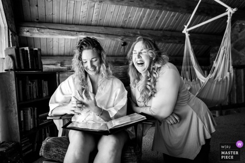 Pagosa Springs, Colorado nuptial day award-winning image of Bride sharing a moment with her mother while looking at a special album in the morning - from the world's best wedding photography competitions hosted by the WPJA