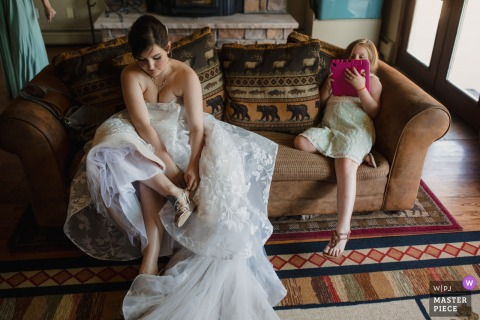 Wedgwood Weddings, Mountain View, Pine, Colorado getting ready for marriage award-winning picture capturing Bride puts her shoes on while her niece plays on her iPad - from the world's best wedding photography competitions held by the WPJA