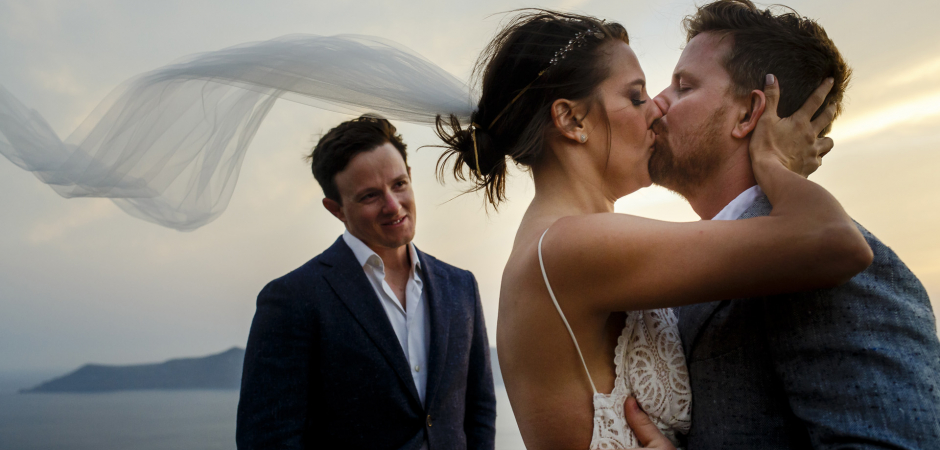 Fira, Santorini, Greece wedding kiss photography from the ceremony by Ufuk Sarisen