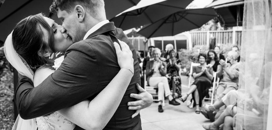 Ein Braut- und Bräutigamkuss von der Hochzeitszeremonie im Freien im Restaurant Pouwe, Hoeven, NL. Fotografie von Caroline Elenbaas