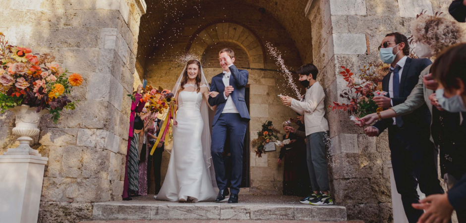 Wedding image of the bride and groom exiting the Abbey of San Galgano, Chiusdino, Siena, Italy - Photography by Alessia Bruchi
