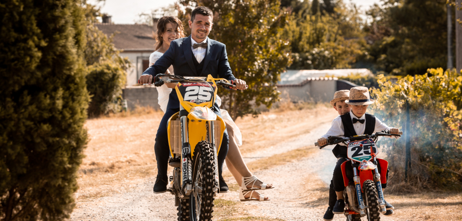 Wedding image of the bride, groom and their kids on motorcycles at a Lescure, France Elopement - Photography by Loic Bourniquel