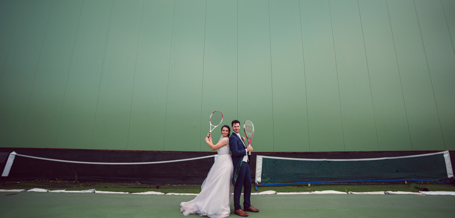 Wedding picture of a couple on a tennis court during their Elopement - Photo by Tatyana Chohadjieva