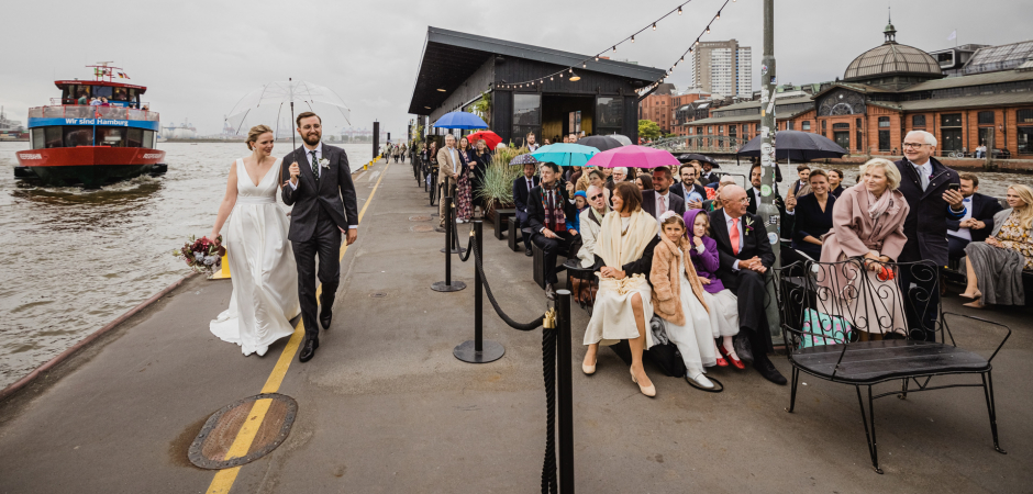Outdoor Marriage Picture of bride and groom walking to ceremony at Hamburg Harbor, Germany Port - Elopement Image by Andrea Sampoli