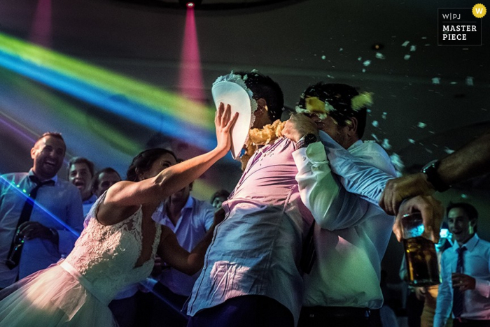 The bride shoves a plate of cake into the groom's face while a guest holds him in this wedding image composed by a Santa Fe, Argentina photographer.