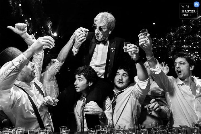 Seven men take shots at the bar together in this black and white photo by a Santa Fe, Argentina wedding photographer.