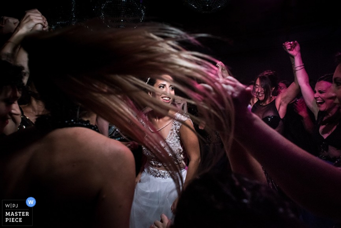 Detail photo of a woman's hair whipping through the air as she and the other guests dance with the bride. Composed by an award-winning Santa Fe, Argentina wedding photographer.