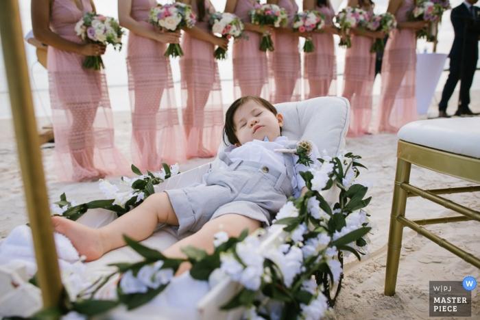 Ein kleiner Junge schläft auf einem von Blumen umgebenen Stuhl, während die Brautjungfern in diesem preisgekrönten Bild, das von einem Hochzeitsfotografen aus Cartago, Costa Rica, aufgenommen wurde, hinter ihm stehen.
