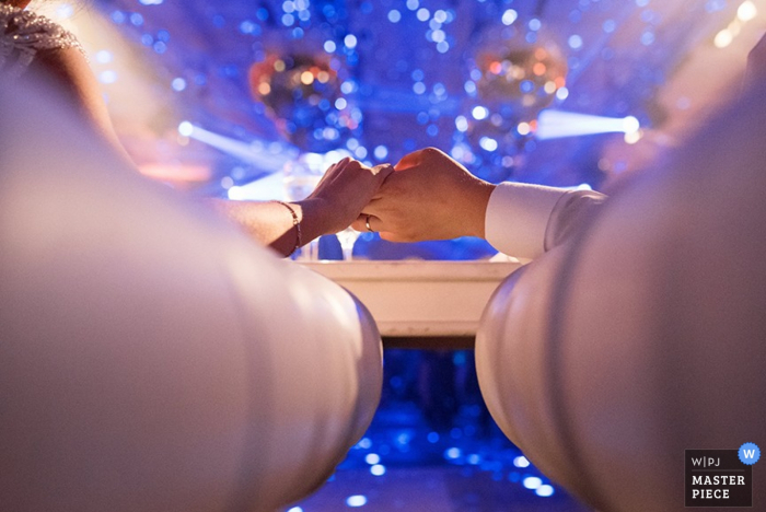 Detail of a bride and groom holding hands, surrounded by blue light. Taken by a Santa Fe, Argentina wedding photographer.