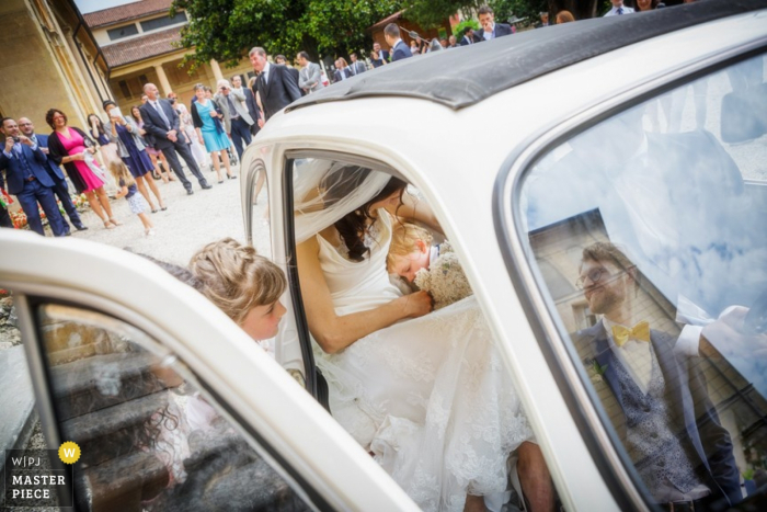 The bride sits in the back of a car with a little boy asleep on her in this wedding photo composed by a Venice photographer.