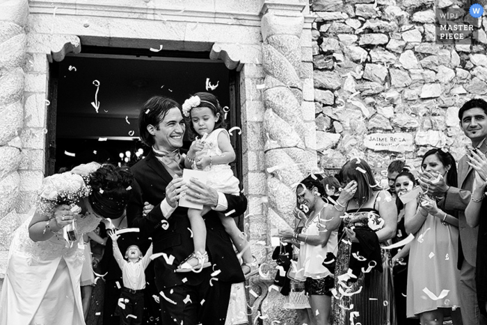 Black and white photo of the bride and groom exiting the ceremony as the groom carries a little girl by a Santa Fe, Argentina wedding photographer.