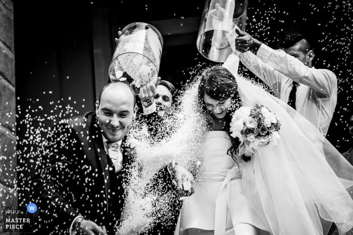 Zwart-witte foto van twee mensen die confettien op de bruid en de bruidegom dumpen door een het huwelijksfotograaf van Lombardije.